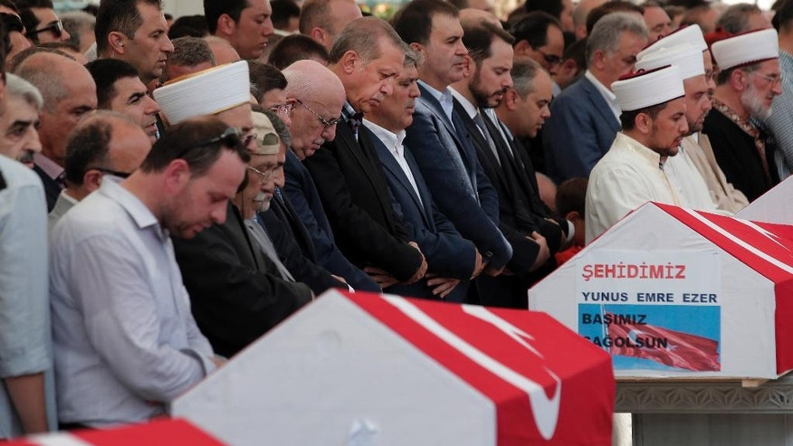 Turkey's President Recep Tayyip Erdogan, centre, joins mourners for prayers during the funeral for people killed Friday while protesting the attempted coup against Turkey's government, in Istanbul, Sunday, July 17, 2016. Rather than toppling Turkey's strongman president, a failed military coup appears to have bolstered Erdogan's immediate grip on power and boosted his popularity. (AP Photo/Lefteris Pitarakis)