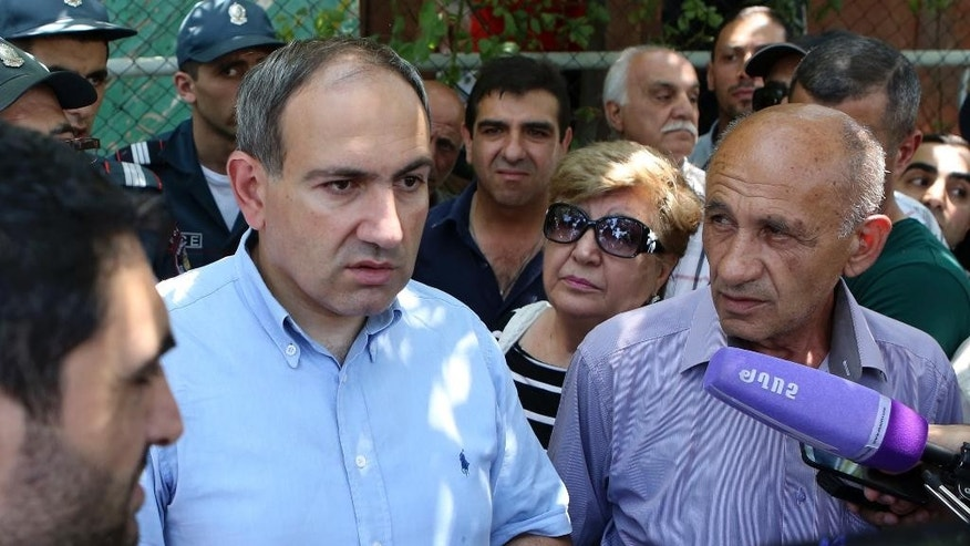 An opposition member of Armenian parliament, Nikol Pashinian, second left, who went to the station to meet with the attackers, speaks to the media at the area near a police station in Yerevan, Armenia, Sunday, July 17, 2016. Armenia security forces say a group of armed men has attacked a central police station in the Armenian capital, killing one officer, wounding two and taking others hostage. (Varo Rafayelyan/PanPhoto via AP)