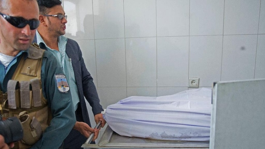 Afghan officials check the body of pregnant Zahra, 14, who is died after she was set on fire in her husband's home, in a hospital in Kabul, Afghanistan, Monday, July 18, 2016. The 45-year-old father, Mohammad Azam, said that he came to the capital Kabul to seek justice for his daughter Zarah. He told The Associated Press that she was tortured with knives and set on fire by her husband's family last week. She died in a Kabul burns hospital on Saturday.  (AP Photos/Massoud Hossaini)