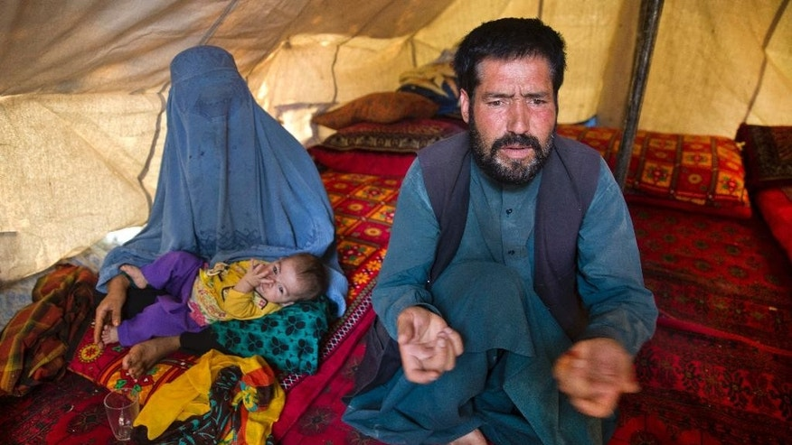 An Afghan man, Mohammad Azam, 45, and father of Zahra, 14, who died after she was set on fire in her husband's home, talks during an interview in a tent in Kabul, Afghanistan, Monday, July 18, 2016.  He said his pregnant 14-year-old daughter was burned to death by her in-laws, the latest reported case of violence against women in the country. (AP Photos/Massoud Hossaini)