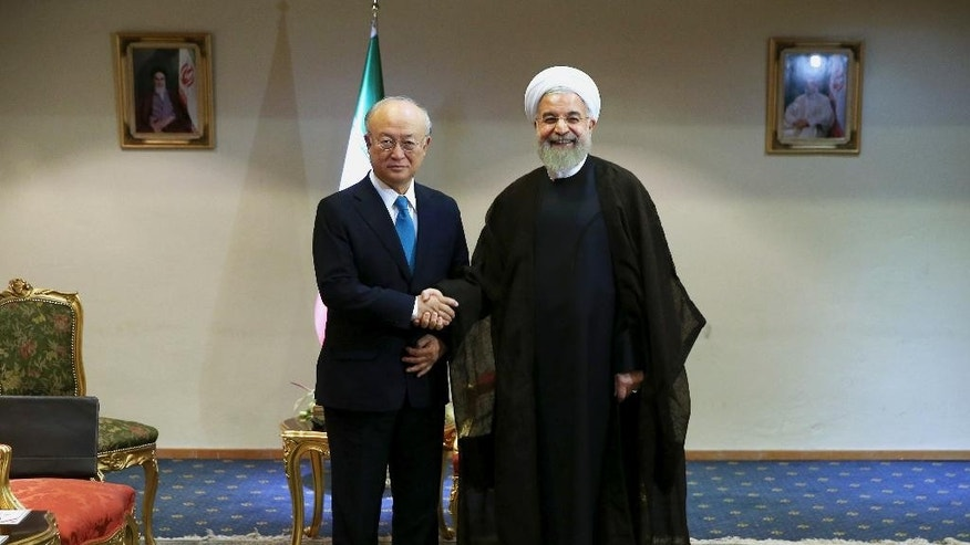 FILE - In this July 2, 2015 file photo, Iran's President Hassan Rouhani, right, shakes hands with the Director General of the International Atomic Energy Agency, IAEA, Yukiya Amano, as they pose for photos at the start of their meeting in Tehran, Iran. A document obtained by The Associated Press Monday, July 18, 2016, says key nuclear restrictions on Iran will ease in a little more than a decade, halving the time Tehran would need to build a bomb if it chose to do so. The document says that 11 to 13 years into the 15-year agreement, Iran can replace the 5,060 inefficient centrifuges it now uses to enrich uranium with up to 3,500 advanced machines. (AP Photo/Ebrahim Noroozi, File)