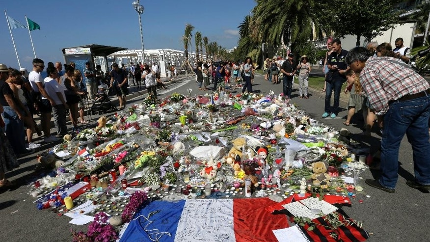 People look flowers placed on the Promenade des Anglais at the scene of a truck attack on Thursday. France is holding a national moment of silence for 84 people killed by a truck rampage in Nice, and thousands of people are massed on the waterfront promenade where Bastille Day celebrations became a killing field. (AP Photo/Claude Paris)