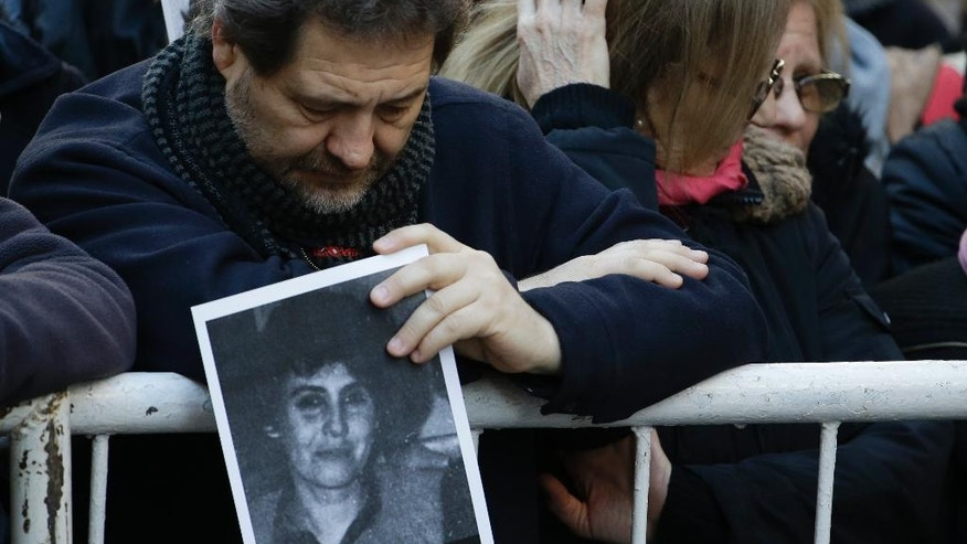 A man holds a picture of a person who died in the bombing of the AMIA Jewish center that killed 85 people as people commemorate the attack's 22nd anniversary in Buenos Aires, Argentina, Monday, July 18, 2016. The 1994 attack is still unsolved. (AP Photo/Natacha Pisarenko)