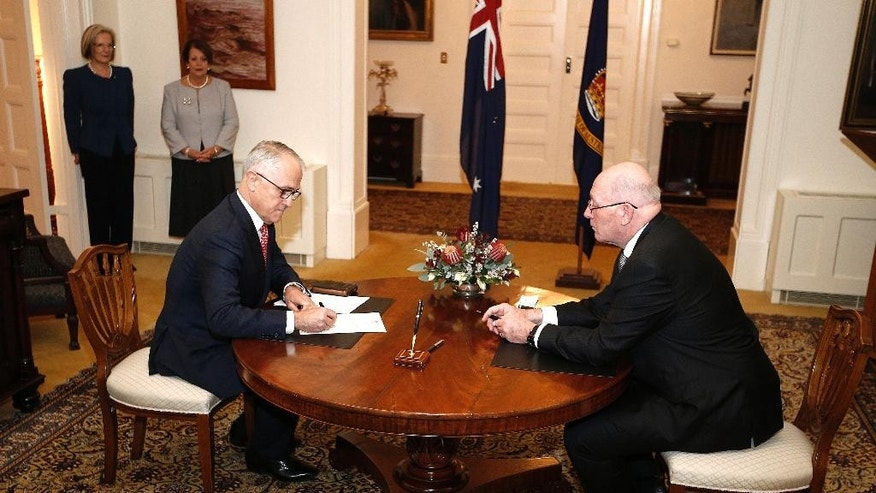 Malcolm Turnbull, left, is sworn in as Australia's prime minister by Governor-General Peter Cosgrove at Government House in Canberra, Australia, Tuesday, July 19, 2016. Australia's new cabinet was sworn in Tuesday, but the conservative government will have the slimmest of majorities when Parliament opens next month. (AP Photo/Rob Griffith)