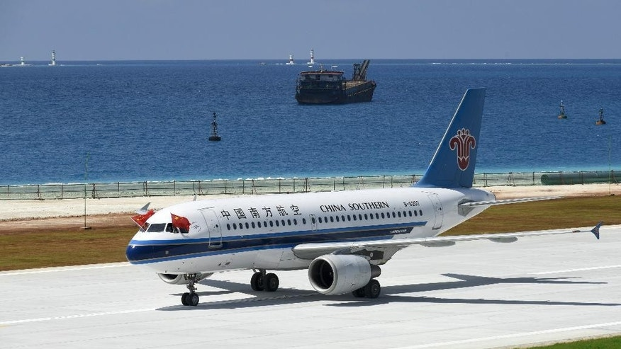 In this July, 13, 2016 photo released by Xinhua News Agency, pilots place Chinese national flags on the cockpit window of China Southern Airlines' passenger jet after it successfully test landed at an airport on the Meiji reef of the Nansha Islands in the South China Sea. China said Monday, July 18, 2016, that it is closing off a part of the South China Sea for military exercises this week, days after an international tribunal ruled against Beijing's claim to ownership of virtually the entire strategic waterway. (Chen Yichen/Xinhua via AP)