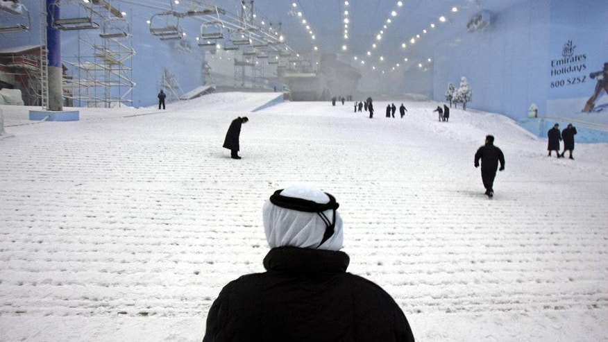 FILE - In this Oct. 25, 2005 file photo, Younis Al Mulla, General manager of Mall of the Emirates & Ski Dubai stands (with back to camera) viewing the snow covered slope at Ski Dubai complex as they have started to make real snow to prepare for the launch of first ski season in Dubai, United Arab Emirates. Visitors to Dubai have a new way to keep cool during the scorching Mideast summer. The company behind the city's indoor ski slope plans to let guests stay overnight in tents on the man-made snow on Fridays starting from July 29, 2016. (AP Photo/Kamran Jebreili, File)