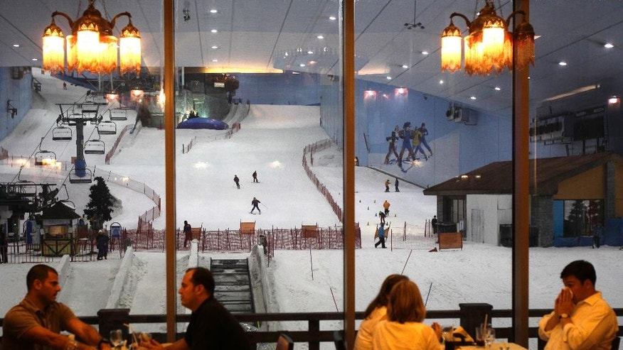 FILE - In this file photo dated Thursday, Aug. 2, 2012, people dine at a Lebanese restaurant overlooking to indoor ski slope in Dubai, United Arab Emirates. It costs at least $49 to tackle the manufactured snow-covered slopes of indoor Ski Dubai. Visitors to Dubai have a new way to keep cool during the scorching Mideast summer. The company behind the city's indoor ski slope plans to let guests stay overnight in tents on the man-made snow on Fridays starting from July 29, 2016. (AP Photo/Kamran Jebreili, File)
