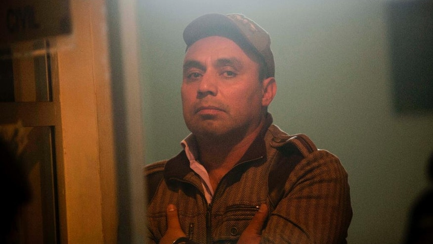 CORRECTS YEAR OF CONVICTION - FILE - In this Feb. 15, 2012 file photo shot through a window, former Guatemalan Army Captain Byron Lima Oliva, accused and sentenced in 2001 to 20 years in prison for the 1998 slaying of Bishop Juan Jose Gerardi, stares into the camera as he waits in a courtroom in Guatemala City. Authorities said on Monday, July 18, 2016 that Lima has died in a prison riot. (AP Photo/Moises Castillo, File)