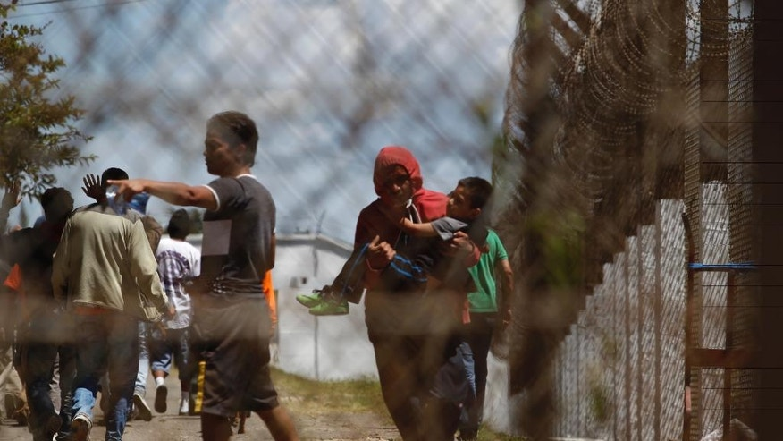 A prisoner evacuates a child, who was visiting the Pavón prison, to a safer place during a prison riot on the outskirts of Guatemala City, Monday, July 18, 2016. Authorities said Byron Lima, the man serving a prison sentence for killing a Catholic bishop, died in the riot. (AP photo/Moises Castillo)