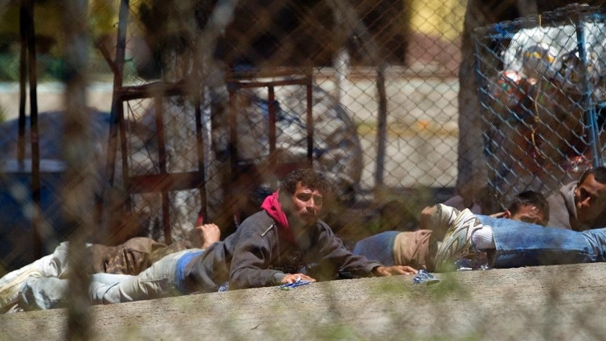 Seen through several chain link fences, people take cover after a riot broke out inside the Pavon prison in Guatemala City, Guatemala, Monday, July 18, 2016. Authorities in Guatemala say Byron Lima, an army captain serving a prison sentence for killing a Catholic bishop, has died during the riot. (AP Photo/Moses Castillo)