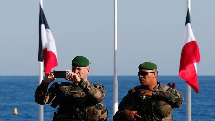 French soldiers patrol on the famed Promenade des Anglais in Nice, southern France, three days after a truck mowed through revelers, Sunday, July 17, 2016. French authorities detained two more people Sunday in the investigation into the Bastille Day truck attack on the Mediterranean city of Nice that killed at least 84 people, as authorities try to determine whether the slain attacker was a committed religious extremist or just a very angry man.(AP Photo/Francois Mori)