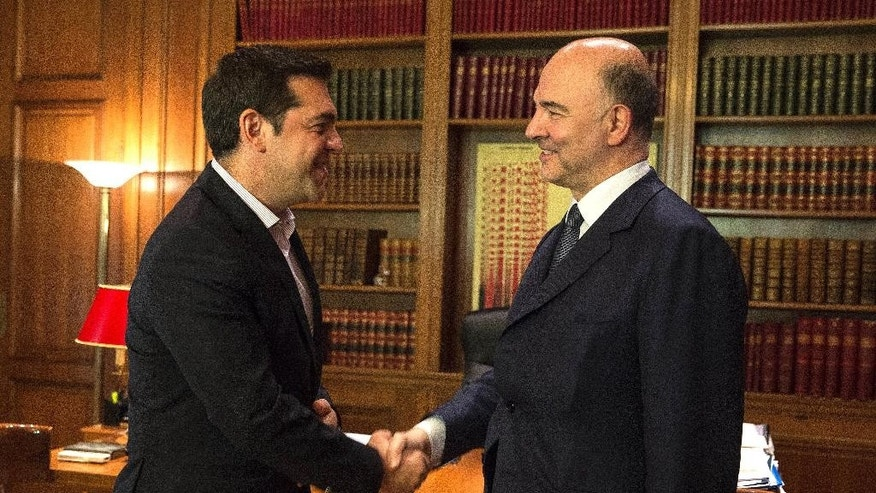 European Union Commissioner for Economic Affairs Pierre Moscovici, right, shakes hands with Greek Prime Minister Alexis Tsipras in Athens, Monday, July 18, 2016. Moscovici is on a one-day visit to Athens where he will also meet with Greek Finance Minister Euclid Tsakalotos. (AP Photo)