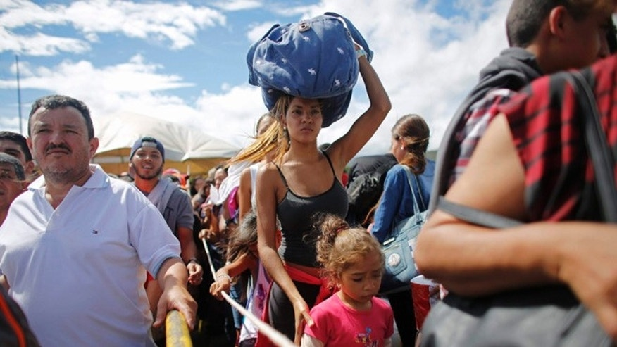 A woman carrying a bundle on her head wait in line to cross the border into Colombia through the Simon Bolivar bridge in San Antonio del Tachira, Venezuela, Sunday, July 17, 2016. Tens of thousands of Venezuelans crossed the border into Colombia on Sunday to hunt for food and medicine that are in short supply at home. It's the second weekend in a row that Venezuelaââ¬â¢s government has opened the long-closed border connecting Venezuela to Colombia. (AP Photo/Ariana Cubillos)