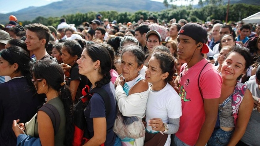 Venezuelans wait in line to cross into Colombia through the Simon Bolivar bridge in San Antonio del Tachira, Venezuela, Sunday July 17, 2016. Tens of thousands of Venezuelans crossed the border into Colombia on Sunday to hunt for food and medicine that are in short supply at home. It's the second weekend in a row that Venezuelaââ¬â¢s government has opened the long-closed border connecting Venezuela to Colombia. (AP Photo/Ariana Cubillos)