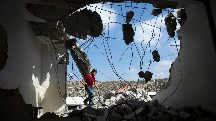 A Palestinian youth walks through rubble the house of Bilal Abu Zeid that was demolished by the Israeli army in the West Bank village of Kabatiya, near Jenin, Monday, July 18, 2016. Abu Zeid is said by the army to have been involved in an attack in Jerusalem in February that killed an Israeli paramilitary police officer. The military did not disclose what role Abu Zeid allegedly played in the attack.(AP Photo/Majdi Mohammed)