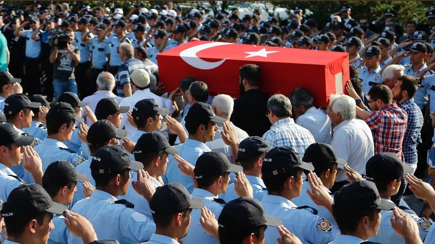 Turkish policemen salute as mourners carry the coffin of a policeman killed on Friday during the failed military coup, at a mass funeral in Ankara, Turkey, Monday, July 18, 2016. Warplanes patrolled Turkey's skies overnight in a sign that authorities feared that the threat against President Recep Tayyip Erdogan's government was not yet over, despite official assurances that life has returned to normal after a failed coup. (AP Photo/Hussein Malla)