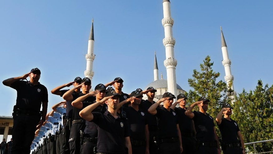 Turkish policemen salute as they attend a mass funeral for their comrades who were killed Friday during the failed military coup, in Ankara, Turkey, Monday, July 18, 2016. Warplanes patrolled Turkey's skies overnight in a sign that authorities feared that the threat against President Recep Tayyip Erdogan's government was not yet over, despite official assurances that life has returned to normal after a failed coup. (AP Photo/Hussein Malla)