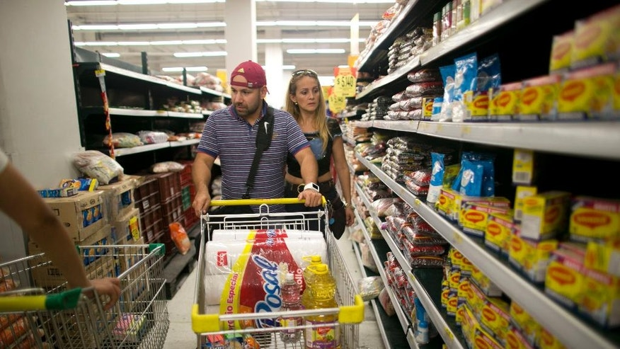 "Ramiro Ramirez pushes a shopping cart as he shops for food with his wife Tebie Gonzalez in Cucuta, Colombia, Sunday, July 17, 2016, during the temporary opening of the long-closed border with Colombia. ""This is money we had been saving for an emergency, and this is an emergency,"" Ramirez said. ""It's scary to spend it, but we're finding less food each day and we need to prepare for what's coming."" (AP Photo/Ariana Cubillos)"