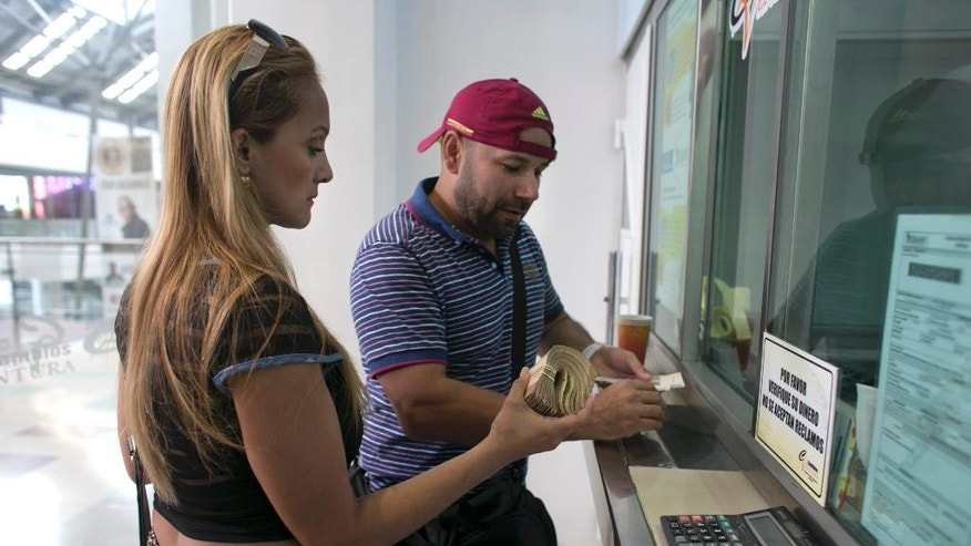 Tebie Gonzalez holds a wad of Venezuelan Bolivar bills as she and her husband Ramiro Ramirez exchange what remains of their savings for Colombian pesos, at a mall before shopping for food in Cucuta, Colombia, Sunday, July 17, 2016, during a temporary opening of the long-closed border with Colombia. Gonzalez earns several times the minimum wage with her job as a sales manager for a chain of furniture stores, but lately her salary is no match for Venezuela's 700 percent inflation. Ramirez's auto parts shop went bust after President Nicolas Maduro closed the border with Colombia a year ago, citing uncontrolled smuggling, and cut off the region's best avenue for imported goods. (AP Photo/Ariana Cubillos)