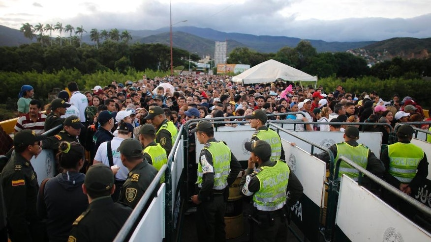 "Venezuelans cross the Simon Bolivar bridge that links San Antonio del Tachira, Venezuela, with Cucuta, Colombia, Sunday, July 17, 2016. More 100,000 Venezuelans crossed what Colombian officials are calling a ""humanitarian corridor"" to buy as many basic goods as possible. (AP Photo/Ariana Cubillos)"