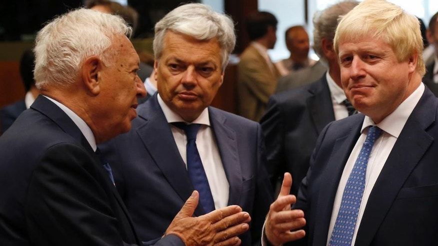Newly appointed British Foreign Secretary Boris Johnson, right, speaks with Belgium's Foreign Minister Didier Reynders, center, and Spanish Foreign Minister Jose Manuel Margallo before the EU foreign ministers meeting at the EU Council building, in Brussels, Belgium, Monday, July 18, 2016. Johnson, who recently likened the European Union to Adolf Hitler's vision for Europe, is in Brussels to meet with his new EU colleagues, and says he hopes to cooperate closely. (AP Photo/Darko Vojinovic)