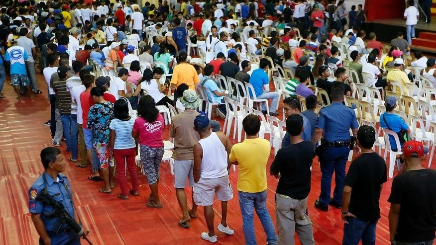More than 1,000 residents queue up in a gymnasium after heeding a call from Tanauan city government to undergo processing allegedly for being drug-users Monday, July 18, 2016 at Tanauan city, Batangas province, south of Manila, Philippines. Philippine President Rodrigo Duterte said he plans to ask Chinese officials why some Chinese citizens who visit his country are involved in illegal drugs. The crime-fighting President, who has vowed to end crimes within six months of taking office on June 30, also said that he will not hesitate to grant pre-signed presidential pardons to law enforcers accused by human rights advocates of abusing their authority in cracking down on narcotics, as long as the soldiers and police involved tell the truth and do not fabricate evidence. (AP Photo/Bullit Marquez)