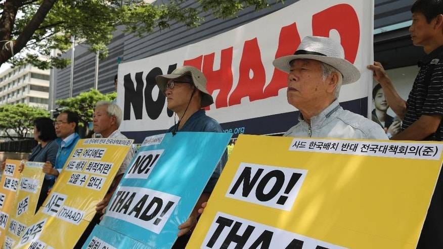 "South Korean protesters hold signs during a rally denouncing a plan to deploy an advanced U.S. missile defense system called Terminal High-Altitude Area Defense, or THAAD, near U.S. Embassy in Seoul, South Korea, Tuesday, July 19, 2016. North Korea on Tuesday fired three ballistic missiles into its eastern sea in an apparent protest of South Korea's decision to allow the deployment of an advanced U.S. missile defense system in the country, Seoul officials said. The letters read ""Stop, to deploy the Terminal High-Altitude Area Defense, or THAAD."" (AP Photo/Lee Jin-man)"