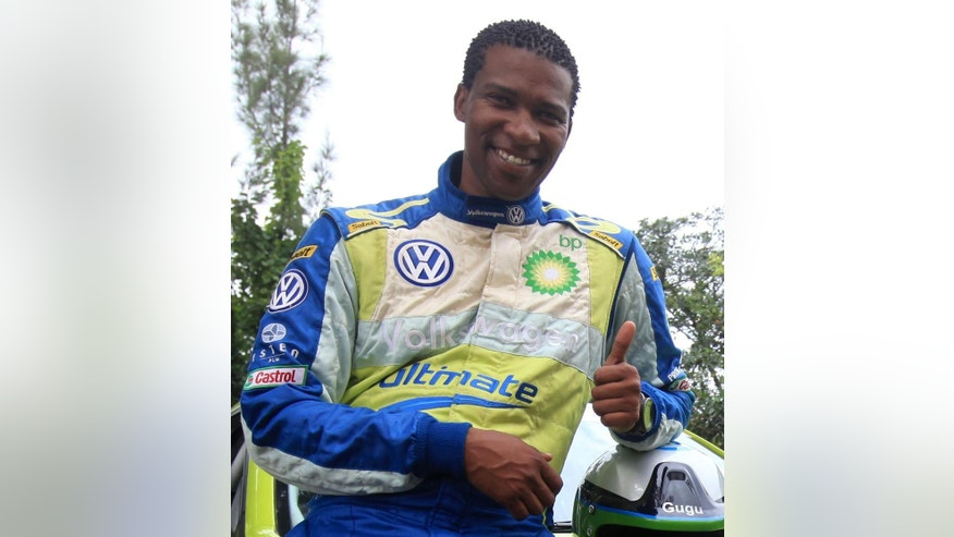 "In this photo taken in 2011, South Africa rally driver Gugu Zulu gestures next to his car. A South African trying to summit Kenya's Mount Kilimanjaro to mark Mandela Day has died. A statement from the Nelson Mandela Foundation said details are ""sketchy"" but that it appeared Gugu Zulu had problems breathing early Monday July 18, 2016, as his group tried to reach Africa's highest peak. (AP Photo)"