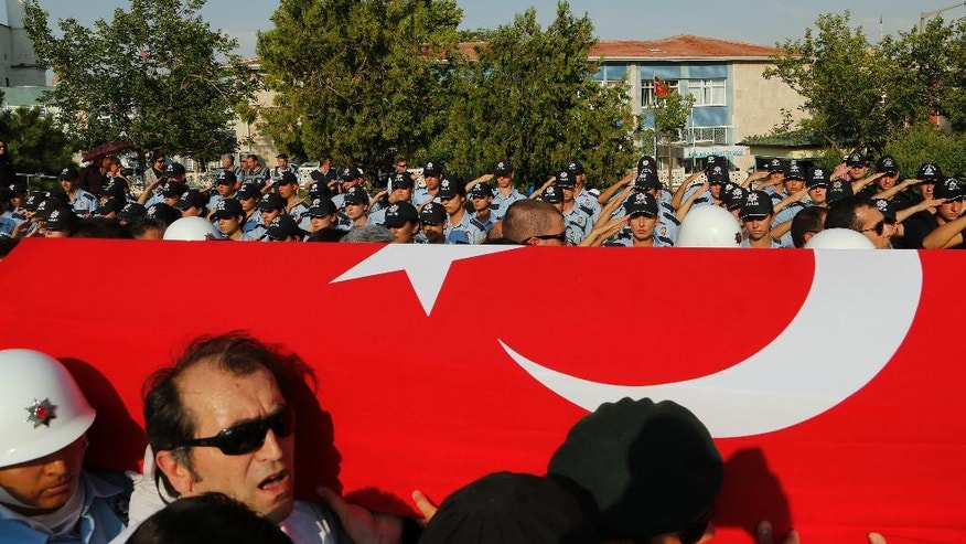 Turkish mourners carry the coffin of a policeman killed Friday in the failed military coup, during a mass funeral in Ankara, Turkey, Monday, July 18, 2016. Warplanes patrolled Turkey's skies overnight in a sign that authorities feared that the threat against President Recep Tayyip Erdogan's government was not yet over, despite official assurances that life has returned to normal after a failed coup. (AP Photo/Hussein Malla)