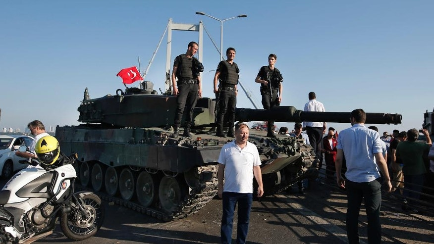 People gather around as Turkish police officers, loyal to the government, stand atop tanks abandoned by Turkish army officers, backdropped by Istanbul's iconic Bosporus Bridge, Saturday, July 16, 2016. Turkish President Recep Tayyip Erdogan declared he was in control of the country early Saturday as government forces fought to squash a coup attempt during a night of explosions, air battles and gunfire that left dozens dead. (AP Photo/Emrah Gurel)