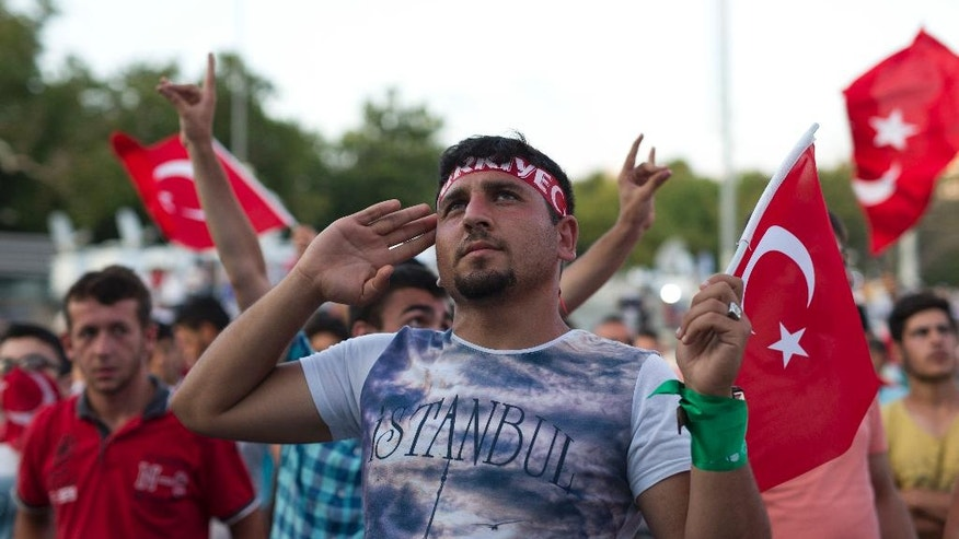 A protester salutes as he takes part in a rally in Taksim Square, Istanbul, Sunday, July 17, 2016. The Turkish government accelerated its crackdown on alleged plotters of the failed coup against President Recep Tayyip Erdogan, with the justice minister saying Sunday that 6,000 people had been detained in the investigation, including three of the country's top generals and hundreds of soldiers. (AP Photo/Petros Giannakouris)