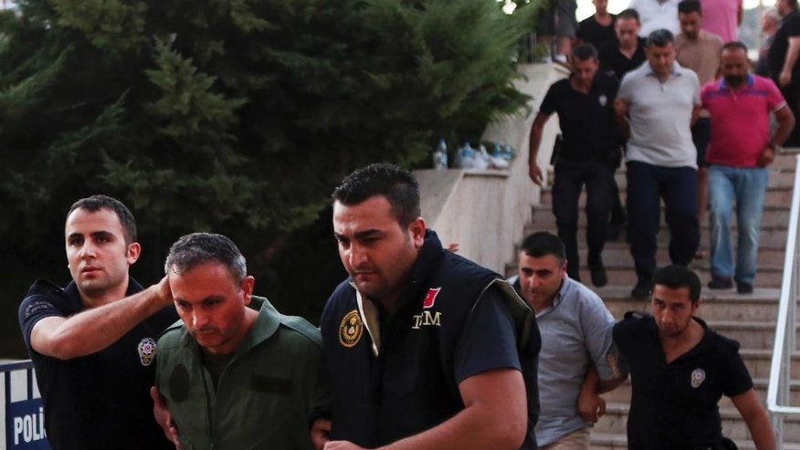 Members of Turkey armed forces are escorted by police for their suspected involvement in Friday's attempted coup at the court house in Mugla, a Mediterrenean city of Turkey, Sunday, July 17, 2016. Following a failed coup against Turkish President Recep Tayyip Erdogan, his government moved swiftly to shore up his power and remove those perceived as an enemy, saying it has detained 6,000 people. (Tolga Adanali/Depo Photos via AP)