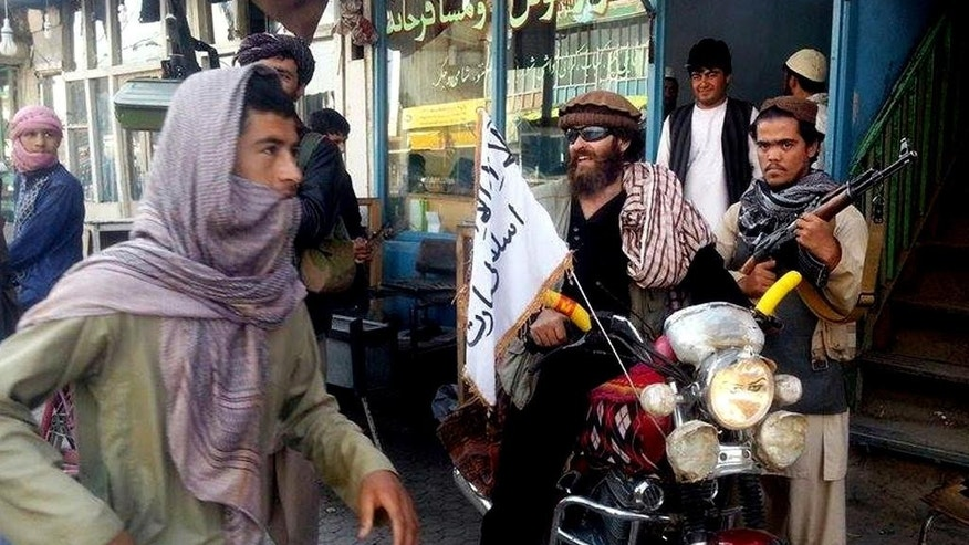 FILE - In this Sept. 29, 2015 file photo, a Taliban fighter sits on his motorcycle adorned with a Taliban flag on a street in Kunduz, Afghanistan. The Taliban launched multiple attacks in Afghanistan, on Tuesday, July 19, 2016, including on a strategic tunnel in the Hindu Kush mountains that links the capital, Kabul, with the country's north and south, officials said. (AP Photo, File)