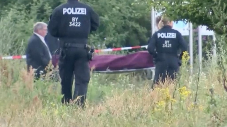 "In this image taken from video police officer look on as the body of a 17-years-old attacker is carried to a hearse in Wuerzburg, southern Germany, Tuesday morning, July 19, 2016. The asylum seeker who shouted ""Allahu akbar"" (""God is great"") during an ax and knife attack on a train, injuring at least five people, had a hand-painted flag of the Islamic State group in his room, a senior German security official said Tuesday. (News5 via AP) GERMANY OUT"