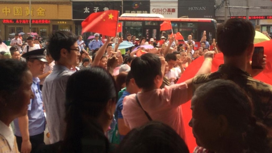 In this photo taken on Tuesday, July 19, 2016 and released by Guo Lu, policemen stand watch Chinese people carrying national flags hold a protest outside a KFC restaurant outlet in Baoying county in east China's Jiangsu province. In an apparent attempt to head off large-scale street demonstrations, Chinese state newspapers have criticized scattered protests against KFC restaurants and other U.S. targets sparked by an international tribunal's ruling that denied Beijing's claim to virtually the entire South China Sea. (Guo Lu via AP)