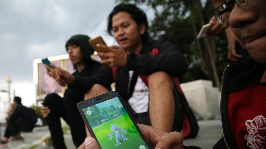 "In this Monday, July 18, 2016 photo, an Indonesian man shows his smartphone as he plays ""Pokemon Go"" in Jakarta, Indonesia. The hugely popular game has sparked a frenzy among Indonesian players despite the application is not officially available in the country. ""Pokemon Go,"" which uses Google Maps and a smartphone to overlay reality with Pokemon creatures, has been a blockbuster hit in the U.S. and other countries where it is available. (AP Photo/Tatan Syuflana)"