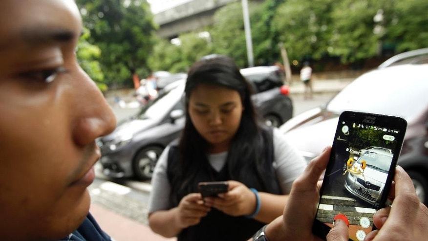 "In this July 18, 2016 photo, Indonesians play ""Pokemon Go"" in Jakarta, Indonesia, Monday, July 18, 2016. The hugely popular game has sparked a frenzy among Indonesian players despite the application is not officially available in the country. ""Pokemon Go,"" which uses Google Maps and a smartphone to overlay reality with Pokemon creatures, has been a blockbuster hit in the U.S. and other countries where it is available. (AP Photo/Achmad Ibrahim)"