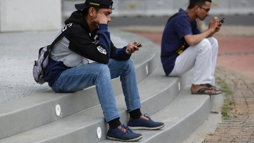 "In this Monday, July 18, 2016 photo, Indonesians gaze at their smartphones as they play ""Pokemon Go"" in Jakarta, Indonesia. The hugely popular game has sparked a frenzy among Indonesian players despite the application is not officially available in the country. ""Pokemon Go,"" which uses Google Maps and a smartphone to overlay reality with Pokemon creatures, has been a blockbuster hit in the U.S. and other countries where it is available. (AP Photo/Tatan Syuflana)"