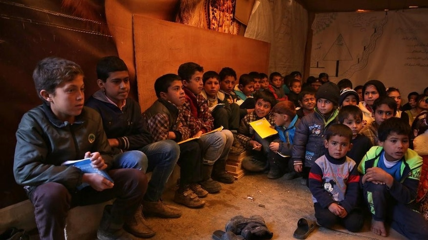 FILE -- In this Wednesday, Jan. 27, 2016 file photo, Syrian refugee children sit on the ground as they listen to their teacher inside a tent that has been turned into a makeshift school, at a Syrian refugee camp in Qab Elias, a village in the Bekaa Valley, Lebanon. Human Rights Watch, a leading international human rights group, said in a report released Tuesday, July 19, 2016, that more than half of the nearly 500,000 school-age Syrian children registered in Lebanon do not go to school and receive no formal education. Since Syria's conflict began in March 2011, hundreds of thousands of Syrians have fled to Lebanon, which is now home to some 1.1 million registered refugees. (AP Photo/Bilal Hussein, File)