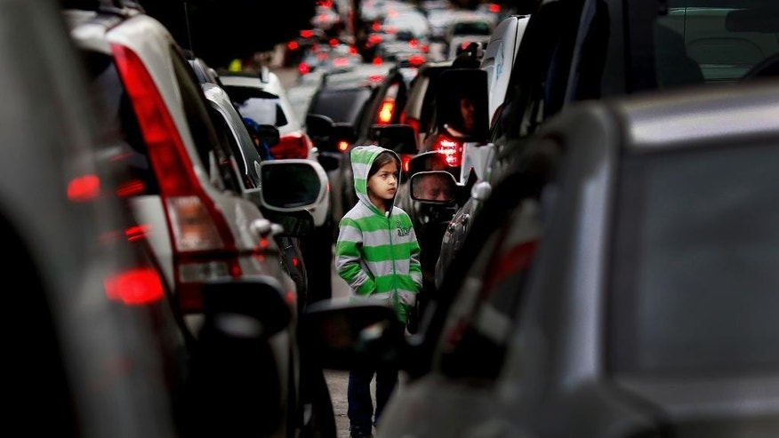 FILE -- In this Feb. 10, 2016 file photo, a Syrian refugee girl begs for money in traffic, in Beirut, Lebanon. Human Rights Watch, a leading international human rights group, said in a report released Tuesday, July 19, 2016, that more than half of the nearly 500,000 school-age Syrian children registered in Lebanon do not go to school and receive no formal education. Since Syria's conflict began in March 2011, hundreds of thousands of Syrians have fled to Lebanon, which is now home to some 1.1 million registered refugees. (AP Photo/Hassan Ammar, File)