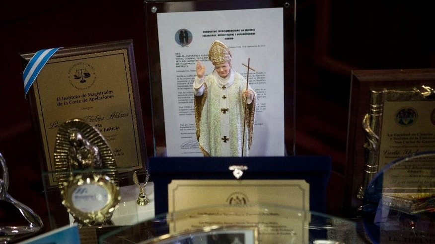 A small statue of the late Pope John Paul II stands by plaques of recognition on the desk of Guatemala's Attorney General Thelma Aldana in Guatemala City, Tuesday, July 19, 2016. Guatemala's chief prosecutor says she believes a recent threat against her is a reaction by organized crime to her work dismantling corruption networks that has landed a former president and VP behind bars. (AP Photo/Moises Castillo)