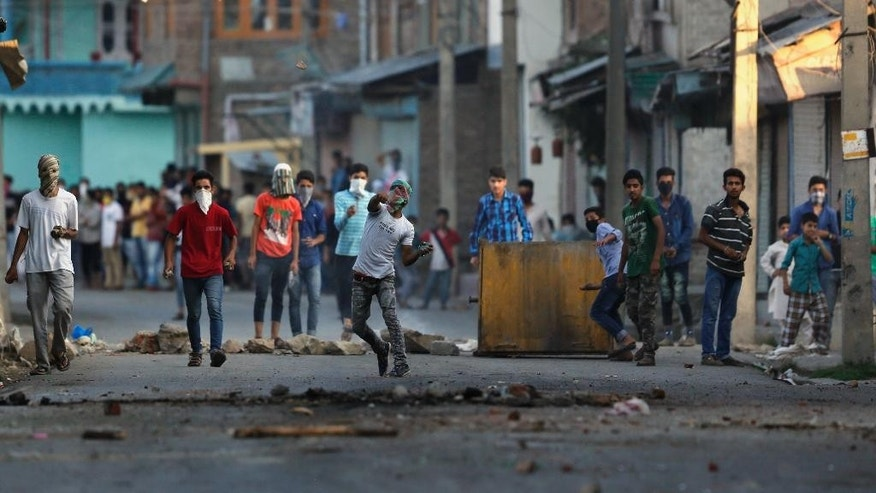 A Kashmiri protester throws a stone at Indian policemen during a protest in Srinagar, Indian controlled Kashmir, Monday, July 18, 2016. A strict curfew was in effect in troubled areas for the ninth straight day Sunday, with hundreds of thousands of people trying to cope with shortages of food and other necessities. Tens of thousands of government troops patrolled mostly deserted streets in the region, where shops and businesses remained closed. (AP Photo/Mukhtar Khan)