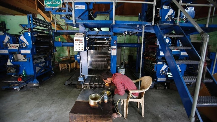Mohammad Ishaq, an employee of the Daily Kashmir Images, has his lunch near the shut down printing press machines on the outskirts of Srinagar, Indian controlled Kashmir, Monday, July 18, 2016. Authorities in India's portion of Kashmir have shut down printing presses and temporarily banned newspapers from publishing in a sweeping information blackout after days of anti-India protests left dozens of people dead in the volatile region after Indian troops killed a popular young leader of the largest rebel group fighting against Indian rule in the region. (AP Photo/Mukhtar Khan)