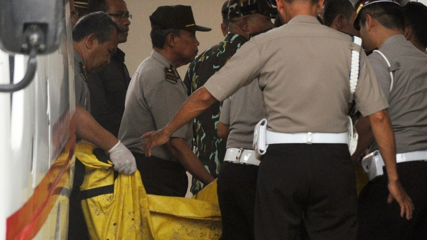 Indonesian police officers arriving at a hospital carry one of the two bodies of militants killed by Indonesian security forces.
