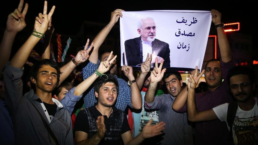 "FILE -- In this July 14, 2015 file photo, young Iranian men cheer and show victory signs while holding a picture of Foreign Minister Mohammad Javad Zarif, reading ""Zarif is Mosaddegh of our time,"" comparing Zarif to Mohammad Mosaddegh, Iran's legendary prime minister during the 1950s who nationalized the country's oil industry, in Tehran, Iran. A document obtained by The Associated Press Monday, July 18, 2016, says key nuclear restrictions on Iran will ease in a little more than a decade, halving the time Tehran would need to build a bomb if it chose to do so. The document says that 11 to 13 years into the 15-year agreement, Iran can replace the 5,060 inefficient centrifuges it now uses to enrich uranium with up to 3,500 advanced machines. (AP Photo/Ebrahim Noroozi, File)"