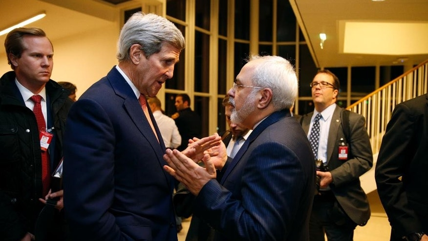 FILE - In this Jan. 16, 2016 file-pool photo, Secretary of State John Kerry talks with Iranian Foreign Minister Mohammad Javad Zarif in Vienna, after the International Atomic Energy Agency (IAEA) verified that Iran has met all conditions under the nuclear deal. A document obtained by The Associated Press Monday, July 18, 2016, says key nuclear restrictions on Iran will ease in a little more than a decade, halving the time Tehran would need to build a bomb if it chose to do so. The document says that 11 to 13 years into the 15-year agreement, Iran can replace the 5,060 inefficient centrifuges it now uses to enrich uranium with up to 3,500 advanced machines. (Kevin Lamarque/Pool via AP, File)