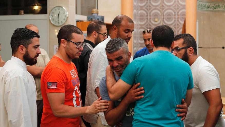 Tahar, center, the father of Kylan Mejri, is comforted by relatives after carrying the coffin of his 4-year-old son at the ar-Rahma mosque in the eastern Nice suburb of Ariane, Tuesday, July 19, 2016, killed in Thursday's truck attack. Tahar's wife Olfa Kalfallah, 31, was also killed. (AP Photo/Francois Mori)