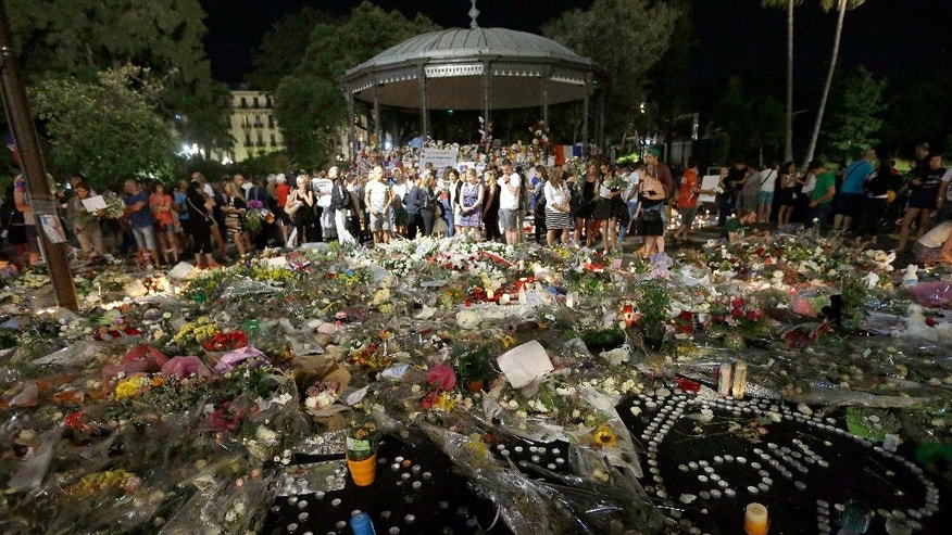 People gather in a new memorial in a gazebo in a seaside park on the famed Promenade des Anglais in Nice, southern France, Monday, July 18, 2016. Mourners formed a human chain to remove flowers, candles and other mementos placed along the Promenade des Anglais as spontaneous memorials to the victims of the Bastille Day attack in preparation to open the westbound lane.(AP Photo/Claude Paris)