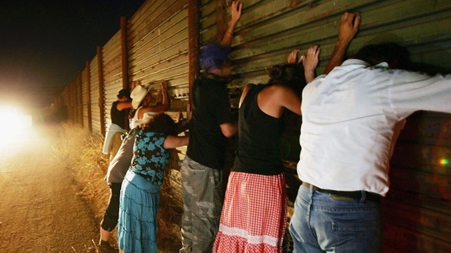 Migrant activists protesting nightly patrols by citizen volunteers who search for people crossing US-Mexico border lean against the border fence to pay homage to illegal immigrants who died crossing over. (Photo by David McNew/Getty Images)