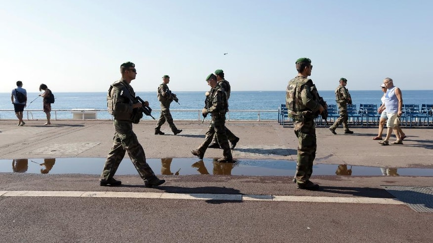 Soldiers patrol on the famed Promenade des Anglais in Nice, southern France, Tuesday, July 19, 2016. Joggers, cyclists and sun-seekers are back on Nice's famed Riviera coast, a further sign of normal life returning on the Promenade des Anglais where dozens were killed in last week's Bastille Day truck attack. (AP Photo/Claude Paris)